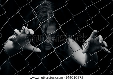 A missing kidnapped, abused, hostage, victim girl alone in emotional stress and pain, afraid, restricted, trapped, call for help, struggle, terrified, threaten, locked in a cage cell try to escape. - stock photo