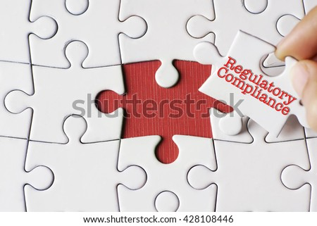 """A missing puzzle with a hand hold a piece of """"regulatory and compliance"""" text puzzle want to complete it - business and finance concept  - stock photo"""