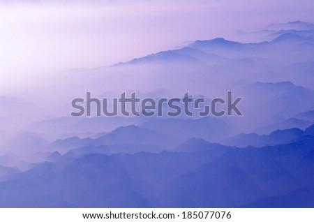 A misty mountain area in shades of blue. - stock photo