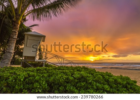A misty, windy sunrise makes a soft colorful sky at a lifeguard stand at Sandy Beach on Oahu, Hawaii - stock photo
