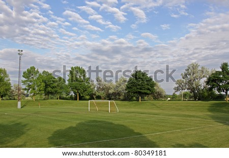 A mixed sky over an unoccupied soccer field with trees in the background. - stock photo