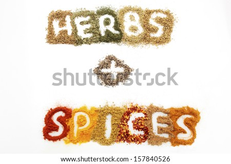 a mixture of different dried herbs and spices on a white background, spelling out the word 'herbs + spices' - stock photo