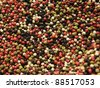 A mixture of red, green, white and black pepper corns. - stock photo