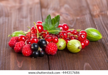 A mixture of ripe berries on a wooden table. Summer Still Life. Raspberries, gooseberries, currants close-up. Stock photo - stock photo