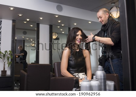 A model gets her hair cut and styled by a hipster hair stylist - stock photo