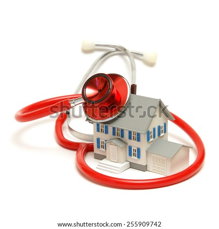 A model house is being doctored by a stethoscope. - stock photo