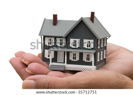 A model house sitting in hands isolated on a white background with clipping path, mortgage help - stock photo