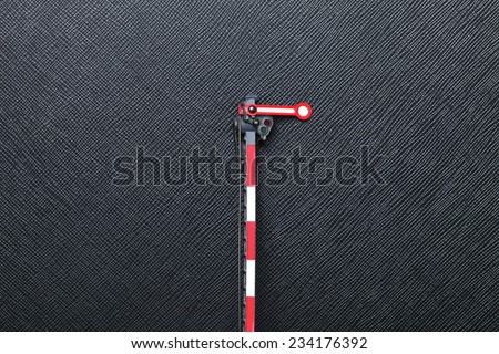 A model of one winged main signal with electricity lantern put on the black color leather surface as a background represent the railway traffic signal system - stock photo