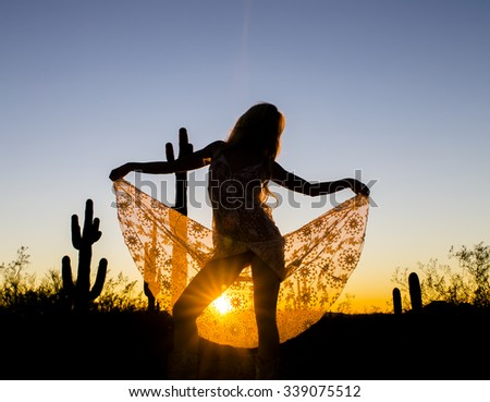 A model posing in the desert of the American Southwest at sunset. - stock photo