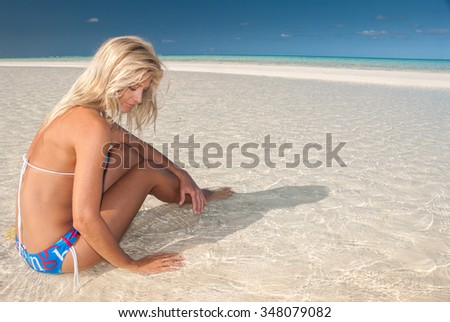 A model sitting in clear ocean water looking at the ripples in the sea - stock photo