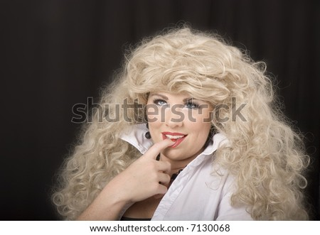 A model wearing a blonde wig and posing for the camera with finger in mouth, looking up
