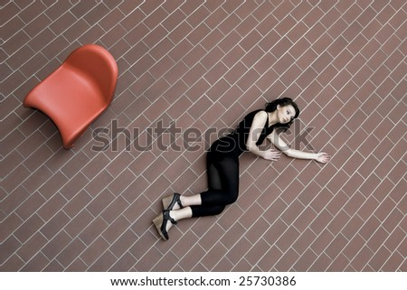 A model who is lying on bricks, red plastic chair next to her. - stock photo