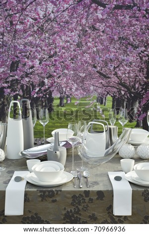 A modern and festive decorated table with white coffee dishware for celebration event in springtime, table in front of beautiful arcade of pink blooming trees - stock photo