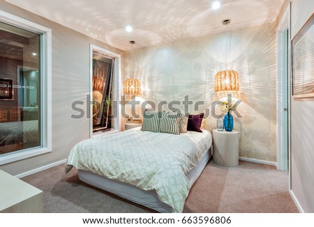 A modern bedroom walls beautifully illuminated with pattern of a light that came through the bamboo or rattan lamps, the room has a huge bed with pillows and some flowers in the blue glass bottles