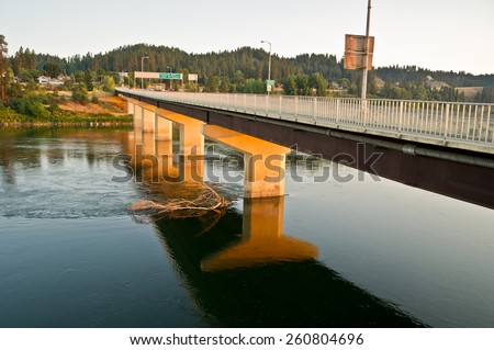 A modern bridge on Highway 95 traveling through Idaho to Canada crosses the Kootenai River in Bonners Ferry, Idaho.  The early morning light creates a beautiful glow on the bridge supports.