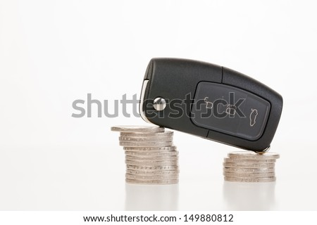 A modern car's remote control starter key standing on two stacks of coins - a concept about car costs or expenses. - stock photo
