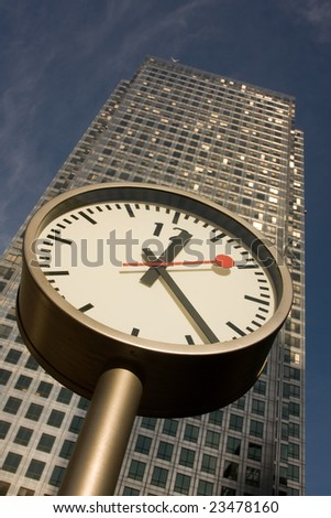 A modern clock outside a famous building in Canary Wharf, London, UK - stock photo