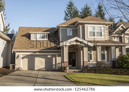 A modern custom built luxury home in a residential neighborhood. - stock photo