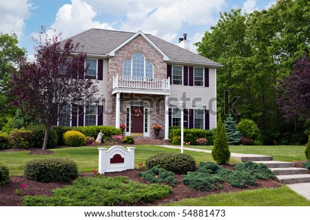 A modern custom built luxury home in a residential neighborhood.  This high end house is very nicely landscaped property. - stock photo