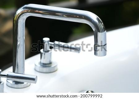 a modern faucet on sink - stock photo