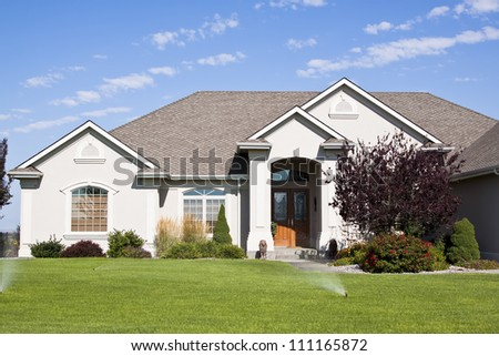 A modern house front entrance with green grass - stock photo