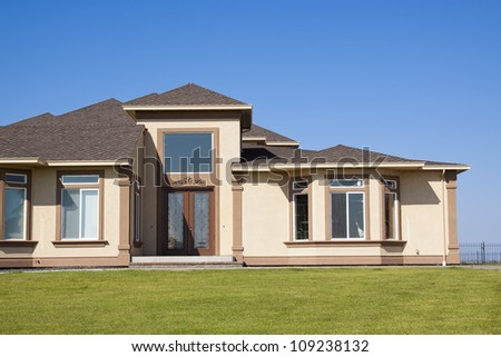 A modern house front entrance with green grass and blue sky - stock photo
