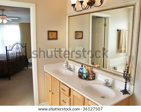 A modern luxurious bathroom with a large in an American home. A bed is visible through the doorway in the background.