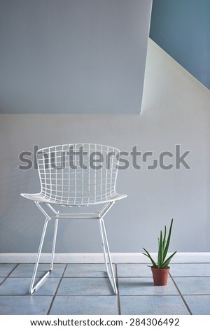 a modern mid century wire chair and a potted plant - stock photo
