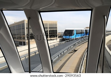 A modern monorail train encountering another monorail train on an elevated track at an airport - stock photo