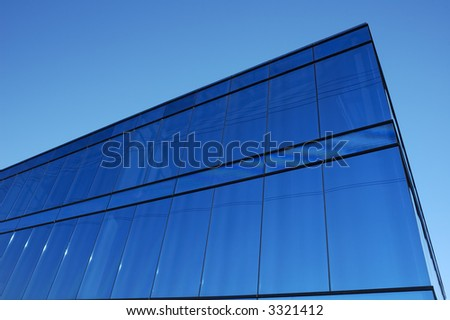 A modern office block with blue glass facade thrusts into the sky