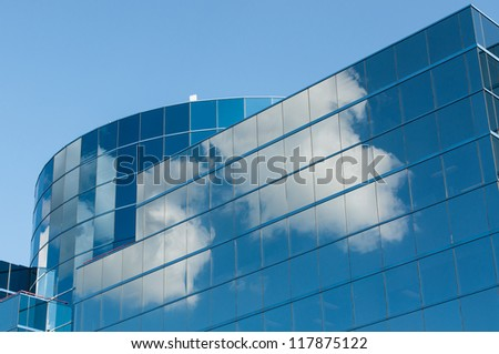 A modern reflective office building reflects the white clouds in a blue sky.