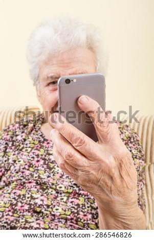 a modern senior woman taking selfie - stock photo