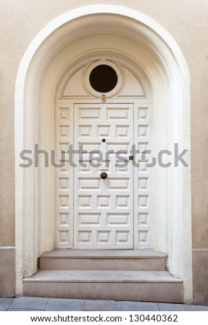 A modern single wooden door painted in white, with a doorknob. The entrance to the building has been placed sligthly receded and above from the street (hence the deep arched frame and the two steps). - stock photo