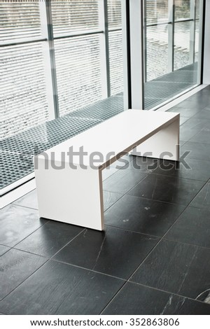 A modern white bench in a commercial building - stock photo