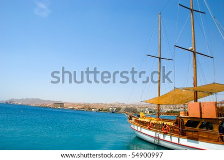 A modern wooden sailboat is prepared for a sail. - stock photo