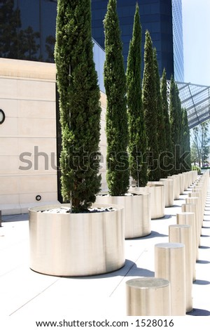 A modernistic walkway lined with stainless steel pillars leading to a Southern California corporate office building