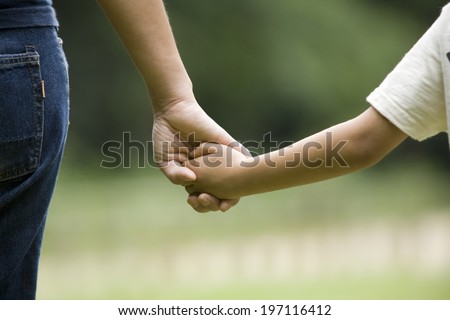 A Mom And Her Child Holding Each Other'S Hand - stock photo