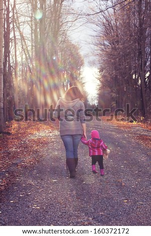 A mom and her daughter illuminated by sun rays filtering through the trees walking down a gravel path surrounded by trees on both sides. - stock photo