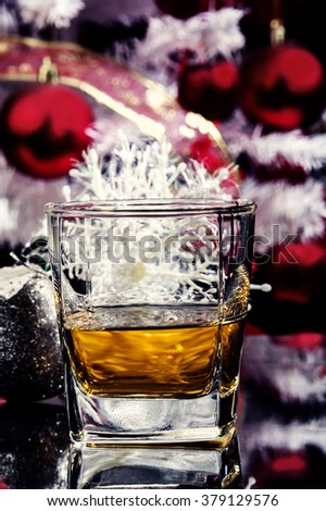 a moment of christmas celebration with glass of whiskey placed on table surrounded by christmas decoration and christmas tree at the background