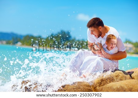 a moment of water splashing on happy father and son - stock photo
