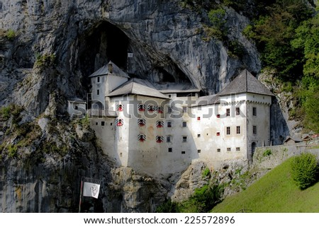 A monastery is tucked into the side of a mountain. - stock photo