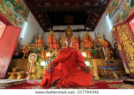 A monk meditating in the lotus position in front of golden Buddhas, low angle
