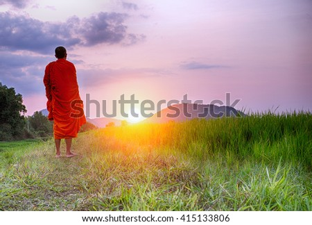 A Monk walks a path towards a setting sun in Cambodia or could be any South East Asian country. This monk's face is not shown and could be any monk. - stock photo