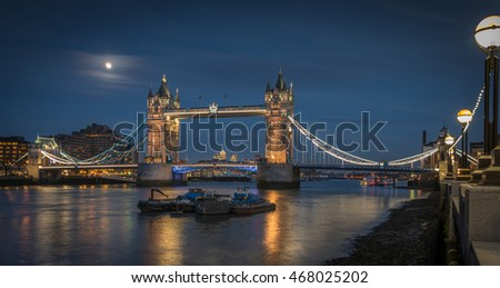 A moonlight shot of the iconic Tower Bridge, London UK. Canary Wharf can be seen in the backgound.
