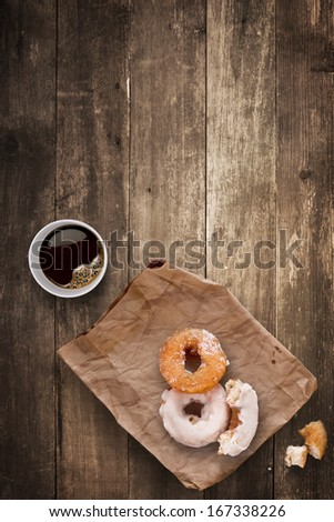 A morning lunch in the office consisted of a cup of black takeaway coffee and tasty donuts. - stock photo