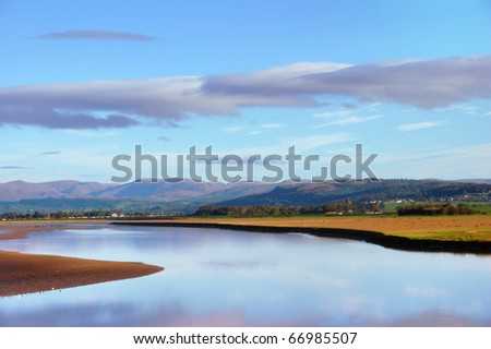 A morning view of the shoreline at Arnside, Cumbria, England, with the Lake District Fells in the distance - stock photo