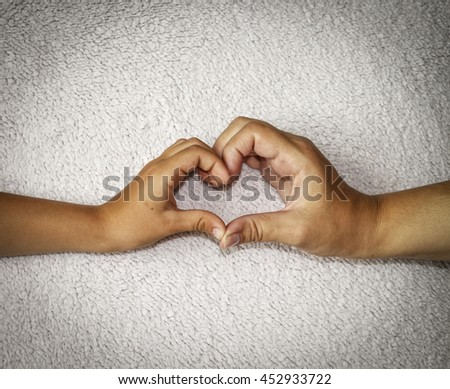 A mother and child made a heart with his hands for a bright home background. - stock photo