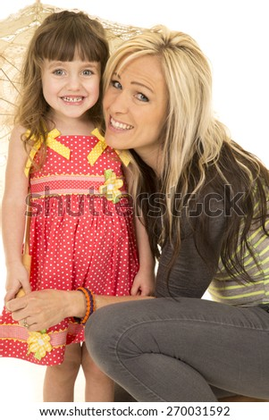 a mother and daughter giving a big smile while the little girl holds an umbrella. - stock photo