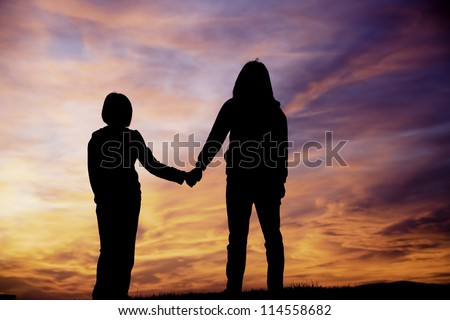 A mother and daughter holding hands watch the sunset. - stock photo