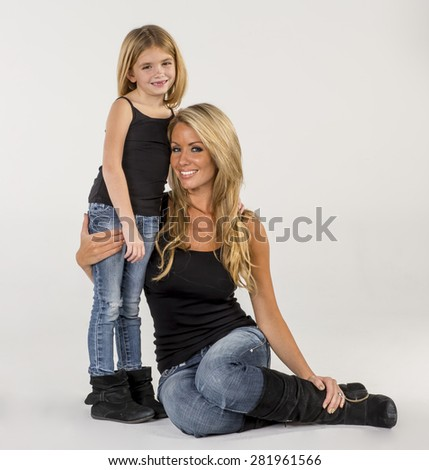 A mother and daughter pose in a studio environment - stock photo